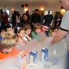 Newburyport:Kids get a kick out of the fog created by liquid nitrogen that  Rob Rothbery of Newburyport uses to make ice cream at the 40th anniversary of the Newburyport Montessori School social held at Nicholson hall in Newburyport Saturday afternoon. JIm Vaiknoras/Staff photo