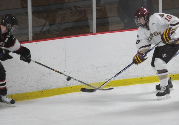Newburyport: Newburyport's Nathan Hickman knocks the puck away from a North Andover player during their game at the Graf Rink in Newburyport Thursday night. Jim Vaiknoras/Staff photo