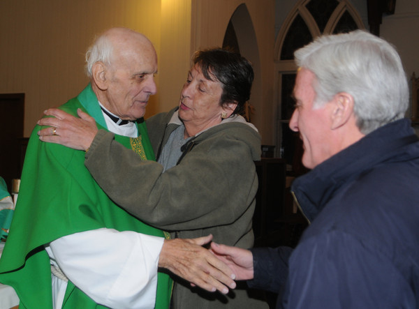 Salisbury :  Rev. Thomas Morgan, longtime pastor of Star of the Sea, greets Joanne and Jack Burke after his final Mass as the church's pastor at the Star of the Sea Beach Chapel Saturday night. Jim Vaiknoras/Staff photo<br /> .