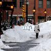 Newburyport: A woman walks her dog down Inn Street through snow piled up from the resent snow. Jim Vaiknoras/Staff photo