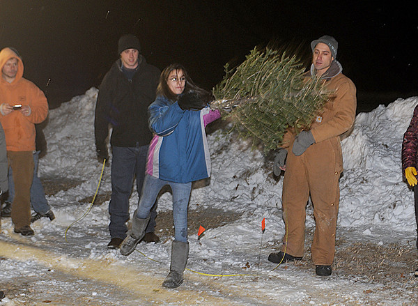 Newbury: Lexi Bellamah , 11, participates in the tree toss at the Old Newbury Christmas Tree Bon Fire Saturday night at the Spencer-Peirce Little Farm in Newbury lights up the night. Residents dropped off over 1000 trees, which were stacked in a pile and torched to the delight of the estimated 2000 people who braved the cold snowy January night. Jim Vaiknoras/Staff photo