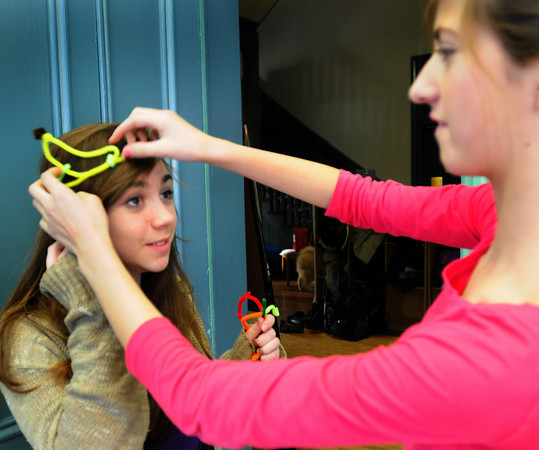 "Newburyport: Claudia Runk, 12, left, puts on a ""fruit hat"" onto Isabella Maginnis' head at the Kelley School Drop-In center Thursday. The girls were in a cigar cleaner constest and were making a couple different scultures to enter. Bryan Eaton/Staff Photo"