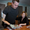 Merrimac: AnnMarie Leary of Angels at Home Healthcare helps Jim Young remove plastic wrap off a plate of lasagna. A fundraiser is being held for the Merrimac man who lost both his arms after being electrocuted while working on a power line as an employee of the Georgetown Light Department. Bryan Eaton/Staff Photo