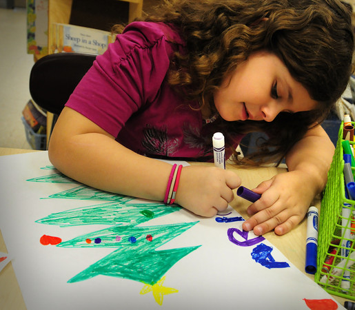 """Amesbury: Ariana Gomez, 6, writes her name on her artwork in Pat Bradley's first grade class at the Cashman School in Amesbury yesterday during """"free draw time."""" She created a Chrismas tree, even though the holiday is over, it's one of her favorite days of the year. Bryan Eaton/Staff Photo"""