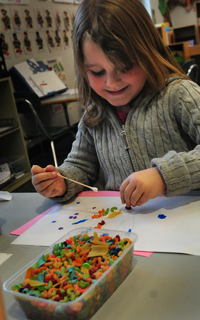 Salisbury: Lily Wilson, 4, glues pieces of colored pasta to paper in Julie Deschene's prekindergarten at Salisbury Elementary School on Wednesday. Not sure what she was creating, she had drawn an outline of her hand and painted the end of where the fingertips would be then started the pasta attachments. Bryan Eaton/Staff Photo