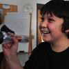 Amesbury: Carter Nichols, 12, shakes a Faraday flashlight which creates electricity as it's shaken using the Law of Induction, just as siesmometer can use the same principal to create a seismogram. The students in Gale Regis' science classes at Amesbury MIddle School were doing different experiments about earthquakes with visiting seismologist Anastasia Moulis from the Weston Observatory. Bryan Eaton/Staff Photo