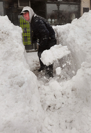 Amesbury: A man who only gave his first name, Scott, shovels a snow bank in front of his apartment in Market Square in Amesbury yesterday afternoon that was as tall as he is. Bryan Eaton/Staff Photo