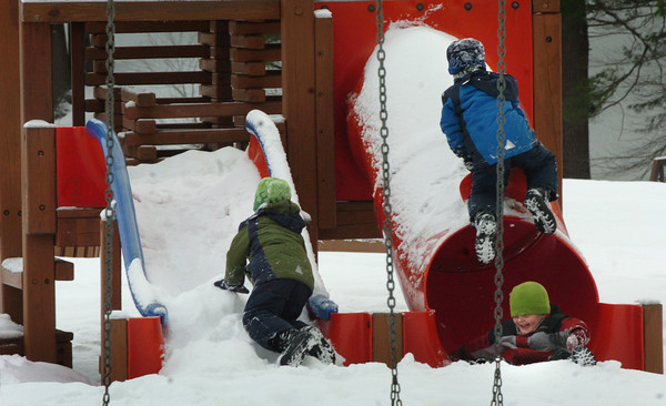 Amesbury: Ethan Berry laughs as he makes it down a tube slide at Amesbury Town Park's playground equipment as friends Michael Sanchez, left, and Max, all 5, have fun in the snow along with Vincent Orrino, out of view. Michelle Sanchez, of Amesbury, mother of the twin boys, is spearheading a drive to spruce up and renovate the park. Bryan Eaton/Staff Photo