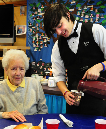 Newbury: Whittier Vocational School student Sean Campbell, 17, pours coffee for Muriel Knight at the Newbury Senior Center on Wednesday. The school's culinary arts students prepared a meal for the group as part of their community outreach program. Bryan Eaton/Staff Photo