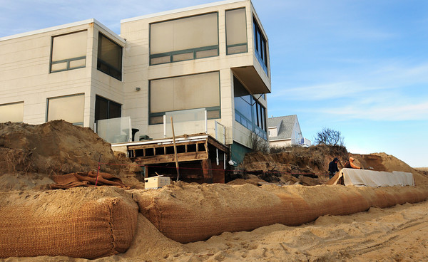 Newburyport: Two workers were constructing more giant sandbags at the Plum Island home of Dr. Sadru Hemani yesterday which has been undermined recently. Bryan Eaton/Staff Photo