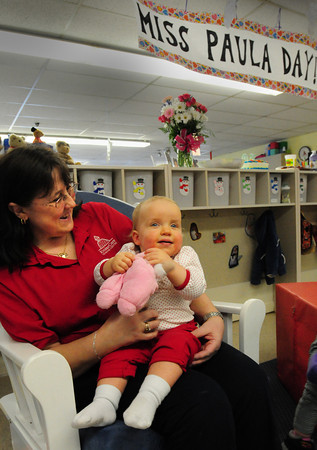 Newburyport: Paula Genna holds Annabelle LeBlanc, 1, on Tuesday morning at KinderCare on Low Street in Newburyport. She celebrated her 30th year at the facility where she has taught children from every age group and for the past five years has been the primary caregiver in the infant program. Bryan Eaton/Staff Photo