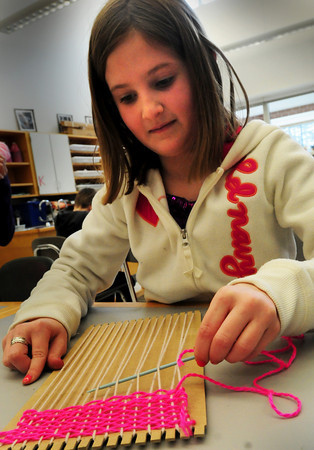 Salisbury: Sheridyn LaRocque, 9, learns the basics of weaving as she makes a wall hanging in Amy Merluzzi's art class at Salisbury Elementary School on Tuesday. Bryan Eaton/Staff Photo