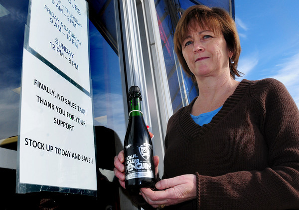 Newburyport: A sign at New England Wine and Spirits in Newburyport thanks those who supported repeal of the sales tax on alcohol. Office manager Joan Regan holds a bottle of Tactical Nuclear Penquin, a 32% alcohol by volume beer from Scotland which sells for $100 a bottle and would have been $106.25 with the old sales tax. Bryan Eaton/Staff Photo
