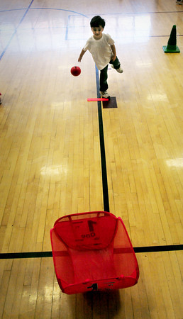Newburyport: Luca Muscarella, 5, tosses a ball into a bucket in Ali Pappas' gym class at the Brown School on Tuesday morning. The kindergartners were tossing underhand at different stations to improve eye to hand coordination. Bryan Eaton/Staff Photo