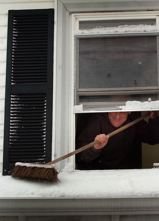 Newburyport: Mark Rosen uses a broom to remove snow on the roof of the entryway to his Fair Street home in Newburyport yesterday morning. Bryan Eaton/Staff Photo