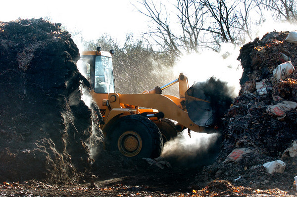 A front-end loader moves piles of leaves and other debris to another area where firefighters hosed down the smoking organic material at the Newburyport composting facility off Crow Lane. Bryan Eaton/Staff Photo