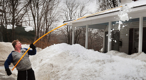 Amesbury: With the rain that fell Tuesday night and yesterday, John Fisher of Congress Street in Amesbury cleaned off the heavy snow from his porch roof. He wasn't taking chances from the extra weight of more snow which is expected tonight into Friday. Bryan Eaton/Staff Photo
