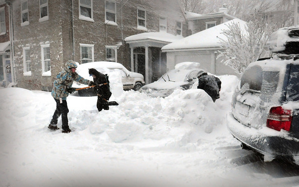 Newburyport: Neighbors on Middle Street in Newburyport shoveled out their cars yesterday morning. Well over a foot of snow fell throughout the area. Bryan Eaton/Staff Photo