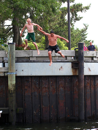 Newburyport: JT Tholman, left, and Jared Sedita, right, both of Newburyport, take a leap into the Merrimack River along the boardwalk Tuesday afternoon, trying to keep cool during their summer vacation. Photo by Ben Laing/Staff Photo