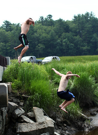 Byfield: Ryan Clay, left, and Derek Ciccione, beat the heat Tuesday morning by jumping in the Parker River in Byfield. Photo by Ben Laing/Staff Photo