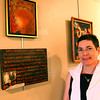 """Newburyport: Elena Ruocco Bachrach, executive director of the Newburyport Art Association, stands with a work in the association's latest exhibition, """"Art and Words"""". Photo by Ben Laing/Staff Photo"""