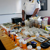 Salisbury: Acting Salisbury police Chief Richard Merrill looks over drugs, including prescription drugs, money and weapons that were confiscated. Bryan Eaton/Staff Photo