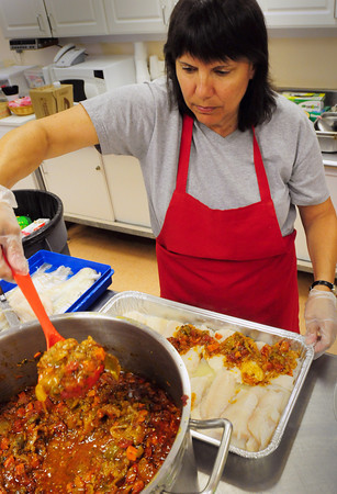 Newburyport: Gina Dussi prepares plaki for the Greek Festival which starts today at Nickerson Hall on Harris Street in Newburyport. The haddock is dipped into lemon juice then topped with a light tomato sauce including chopped, carrot, onion, celery, peppers and herbs and baked. Bryan Eaton/Staff Photo