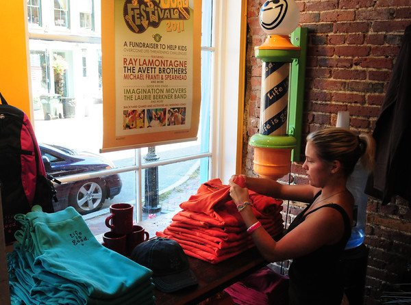 Newburyport: Sales clerk Olivia Listro, Newburyport, at Life is Good on State Street in Newburyport refolds a sweatshirt. Sales have been down in several shops this summer, some are  hoping they get a boost from Yankee Homecoming. Bryan Eaton/Staff Photo