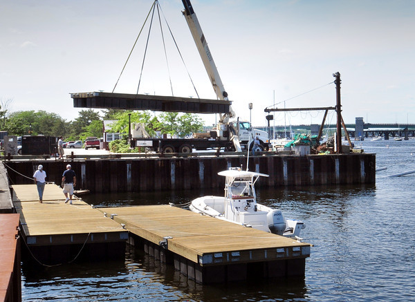 Newburyport: One of four new docks is lowered into place and will be installed in front of the Newburyport Harbormaster's shed on the Merrimack River. The docks were purchased by the Harbor Commission's enterprise fund. Bryan Eaton/Staff Photo