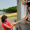 Amesbury: Lisa O'Keefe hands Safiya Tarbell, 7, of Amesbury and ice cream bar at the snack bar at Lake Gardner Beach in Amesbury.  The long-closed stand has been reopened with Maggie Sundae as the tenant. Bryan Eaton/Staff Photo