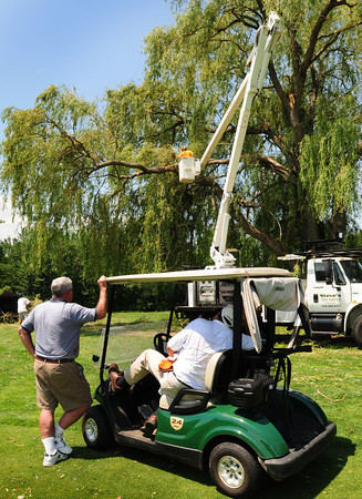 Newbury: Ould Newbury Golf Club members watch as a crew from Steve's Tree Service removes damaged limbs on a willow tree, a victim of Monday night's wind storm. Bryan Eaton/Staff Photo