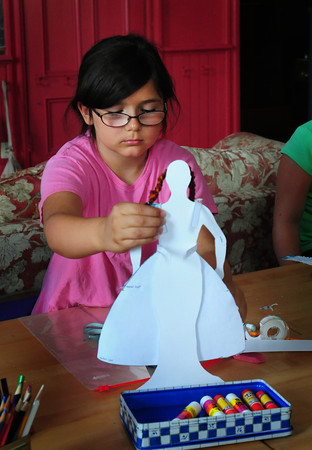 Newburyport: Caroline Tiernan, 9, holds a piece of fabric against a doll cut-out at the Kelley School Youth Center in Newburyport on Wednesday morning. She was in a Junior Fashion Class taught by Elizabeth Rush, part of the Newburyport Youth Services summer program. Bryan Eaton/Staff Photo