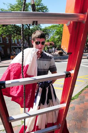 Newburyport: Kyle Mooers of Union Flag Co. in Hampton Falls, N.H. started hanging bunting on State Street on Thursday to ready Newburyport for Yankee Homecoming which starts this weekend. Bryan Eaton/Staff Photo