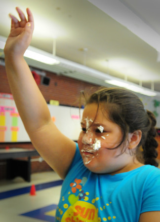 Salisbury: Abbrielle Carrera, 9, raises her hand as she finished diving face first into a plate of whipped cream to find a piece of bubble gum at the Boys and Girls Club on Wednesday, one of the many whacky activities there this week. Bryan Eaton/Staff Photo