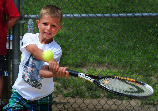 Amesbury: Nico Cusick, 7, of Amesbury swings a tennis racquet during a game of tennis baseball, making it to first base yesterday, at the Amesbury Town Park in the summer recreation program there. Bryan Eaton/Staff Photo