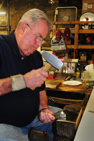 Amesbury: Hammering a piece of silver that will become a spoon, Bob Lapham is retiring after 48 years as a silversmith at Ould Newbury Crafters. Bryan Eaton/Staff Photo
