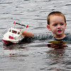 Amesbury: Ethan Klucznik, 3, of Amesbury cruises along Lake Gardner Beach with a model lifeguard boat on Wednesday afternoon. He met some other youngsters who had boats as well all the while cooling off. Bryan Eaton/Staff Photo