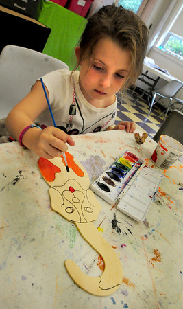 Salisbury: Cassidy Anderson, 6, paints a dog cut-out that will be a decoration to hand from a doorknob at her home on Monday. She was in the arts room at the Boys and Girls Club. Bryan Eaton/Staff Photo
