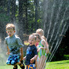 Amesbury: Children run through a sprinkler yesterday morning trying to cool off at Amesbury Town Park. They were in the town's recreation department's Summer Program. Bryan Eaton/Staff Photo