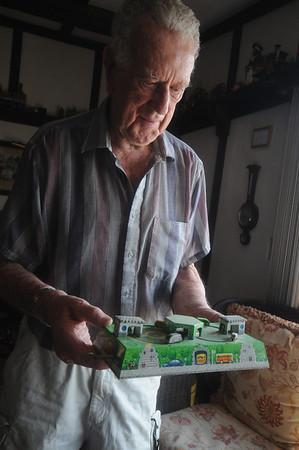 Newbury: Chester Martin looks a tin German wind up toy at his Plum Island home. Jim Vaiknoras/staff photo