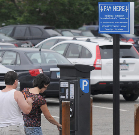 Newburyport: People feed money to the parking machine at the Waterfront  East lot in Newburyport Sunday afternoon. Jim Vaiknoras/Staff photo