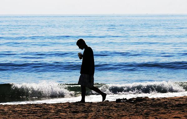 Salisbury: Dave Galvin walks along Salisbury Beach early Saturday morning. Jim Vaiknoras/Staff photo