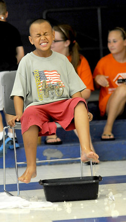 Salisbury: Lebron Miller, 7, of Seabrook, reacts as he tries to pick up a peeble in a bucket of ice water during a game of Cold Feet at the Boys and Girls Club in Salisbury Friday. Jim Vaiknoras/Staff photo