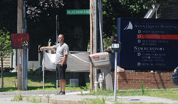 Newburyport: A union worker hold a sign protesting Anna Jaques Hospital on Low Street next to a sign equating unions with communism. Jim Vaiknoras/Staff photo