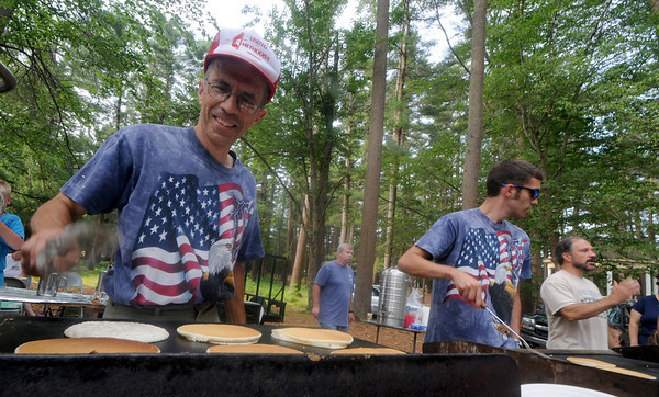Amesbury: Tom Hodges flips pancakes at annual Pancakes Under the Pines in Amesbury Monday morning. Jim Vaiknoras/Staff photo