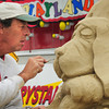 Salisbury: Steve Topazio of Tiverton, R.I., does some detail work on one of several canine-themed sand sculptures at Salisbury Beach on Tuesday morning. The sculptures are for the upcoming Sand and Sea Festival, one of the events being Dog Days of Summer complete with a parade of people's pooches. Bryan Eaton/Staff Photo