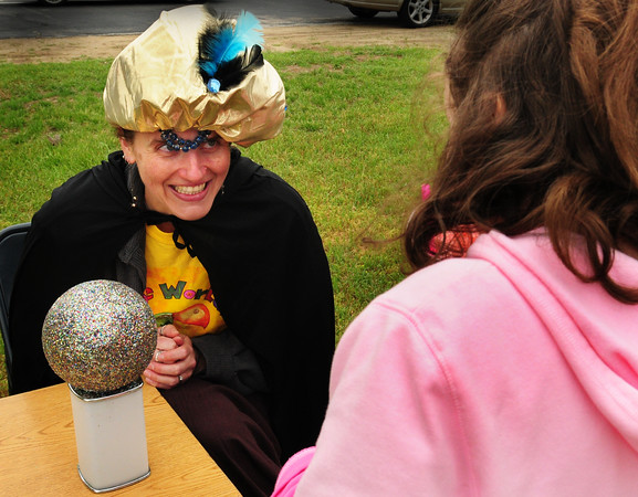 Seabrook: Seabrook Public Library assistant Children's Librarian Lisa Michaud, moonlighting as a fortune teller, predicts Rhiannon Phillips' summer fun. The two were at a Reading Carnival at Seabrook Elementary School on Tuesday where children received tickets for the amount of reading they did at home to redeem at the carnival for games and snacks. Bryan Eaton/Staff Photo