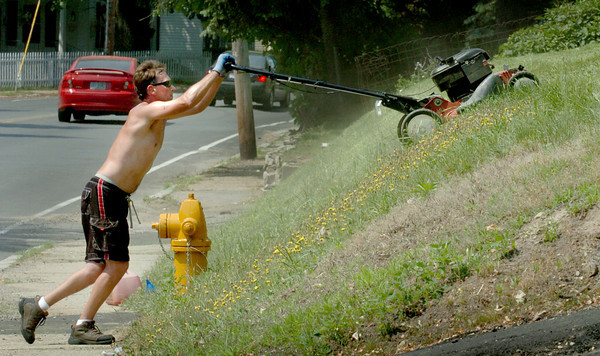 Amesbury: Jason Lovejoy uses a lot of elbow grease to mow his lawn at Elm Street in Amesbury near Atlantic Avenue, many homes in that area with similar slopes. Years ago his grandfather used to lower a lawnmower tied to a rope to get the job done. Bryan Eaton/Staff Photo