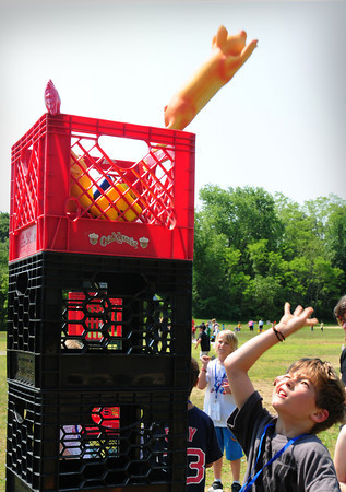 Newburyport: Ian Keller, 8, throws rubber chickens and pigs into milk crates in the Crate Tower at the Bresnahan School's Field Day on Thursday. After each student tossed in the animals, the crate was lifted higher and higher making it more difficult. Bryan Eaton/Staff Photo