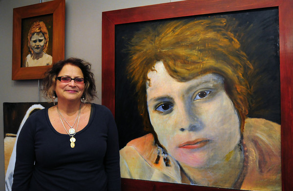 Newburyport: Artist Paula Estey with a self-portrait of an earlier period of her life is part of her show at the Coombs Gallery at the Newburyport Art Association. Bryan Eaton/Staff Photo